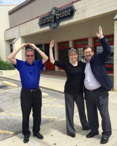 Board members Brian Latta, Lori Ellison-Zuercher and Bryce Matteson flash O-U in front of Blarney Stone Pub